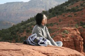 Man meditating outdoors on the rocks.