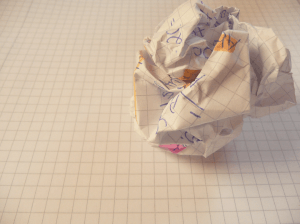 A writer's discarded draft - crumpled paper sheet on the floor.