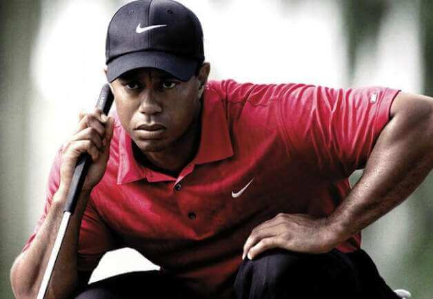 Tiger Woods lining up a golf shot, visualizing the putt going in.